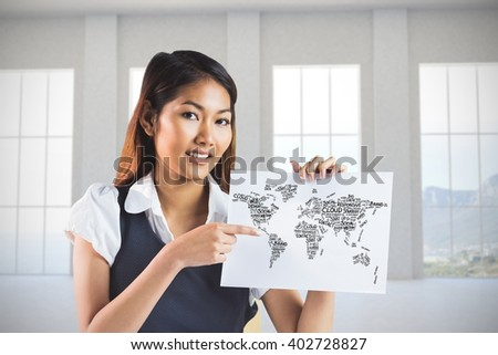 Smiling businesswoman pointing a sheet of paper against room overlooking ocean - stock photo