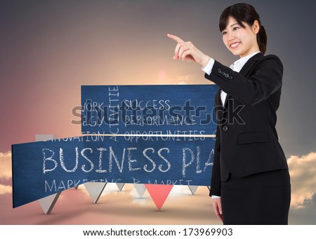 Smiling businesswoman pointing against red and grey arrows pointing against sky - stock photo