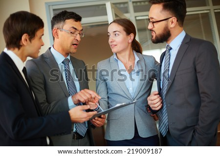 Smiling businesswoman pointing at document and looking at one of colleagues explaining his idea to employees - stock photo