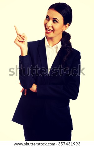 Smiling businesswoman pointing up at copyspace. - stock photo