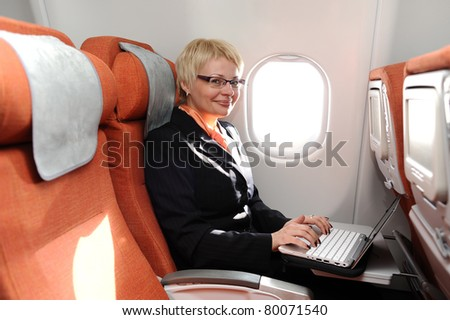 smiling businesswoman posing with laptop on the board of plane - stock photo
