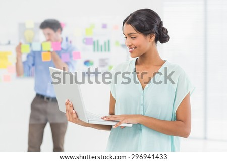 Smiling businesswoman presenting laptop screen with colleague behind her in the office - stock photo