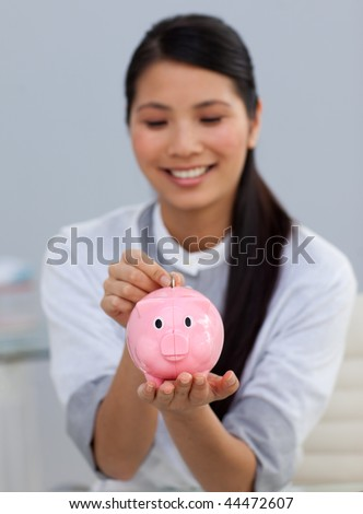 Smiling businesswoman saving money in a piggybank in the office - stock photo