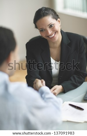 Smiling businesswoman shaking hands (soft focus) - stock photo