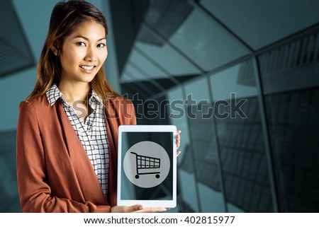 Smiling businesswoman showing a tablet against skyscraper - stock photo