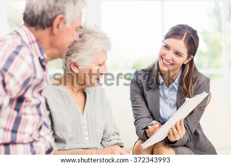 Smiling businesswoman showing documents to senior couple in living room - stock photo