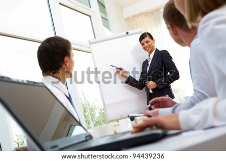 Smiling businesswoman showing her colleagues a new project - stock photo