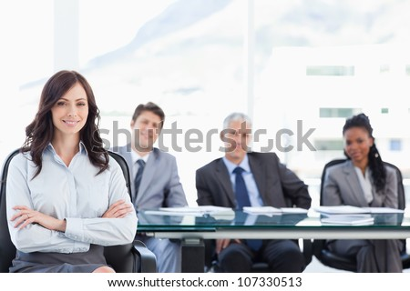 Smiling businesswoman sitting and crossing her arms while accompanied by her team - stock photo