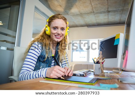 Smiling businesswoman sitting at her desk and listening music in the office - stock photo