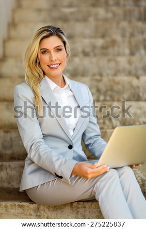 smiling businesswoman sitting on stairs with laptop computer - stock photo