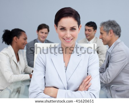 Smiling businesswoman smiling in a meeting with her colleagues working in the background - stock photo