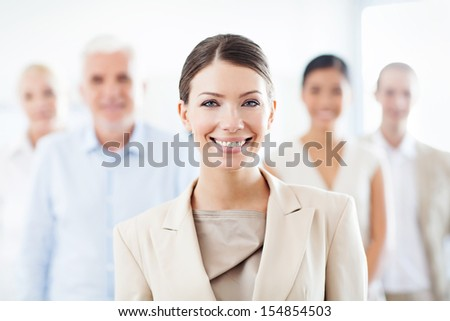 Smiling businesswoman standing in front of her business team. - stock photo