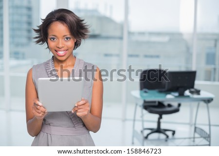 Smiling businesswoman standing in her office and holding tablet while looking at camera - stock photo