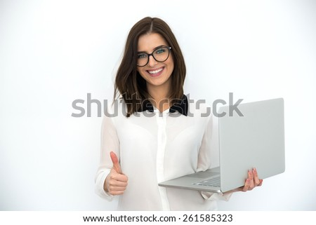 Smiling businesswoman standing with laptop and showing thumb up, with vignette - stock photo