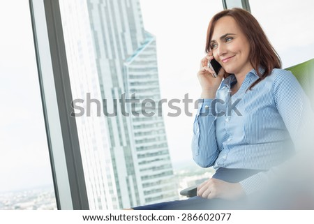 Smiling businesswoman talking on cell phone in office - stock photo