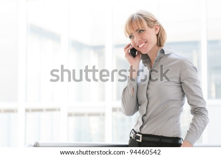 Smiling businesswoman talking on mobile phone in a modern office - stock photo