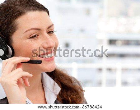 Smiling businesswoman talking on the phone with headphones on in an office - stock photo