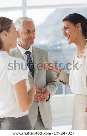 Smiling businesswoman telling something to her colleagues in the office - stock photo