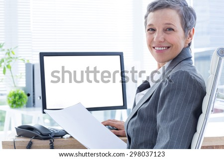 Smiling businesswoman using computer at the office - stock photo