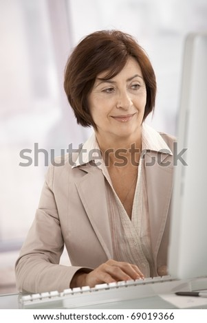 Smiling businesswoman using desktop computer in office.? - stock photo