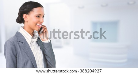 Smiling businesswoman using mobile phone against modern room overlooking city - stock photo
