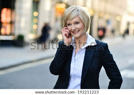 Smiling businesswoman using mobile phone on street - stock photo