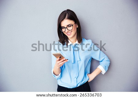 Smiling businesswoman using smartphone over gray background. Wearing in blue shirt and glasses. - stock photo