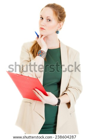 smiling businesswoman wearing a green dress and jacket corrects document - stock photo