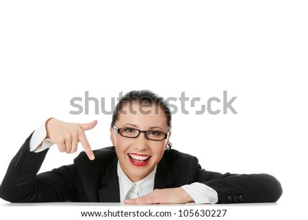 Smiling businesswoman wearing black suit is sitting and pointing at down. Isolated on the white background. - stock photo