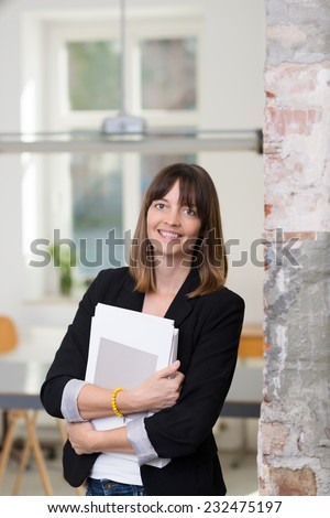 Smiling businesswoman with an armful of papers standing alongside a wall in the office looking at the camera with a friendly smile - stock photo
