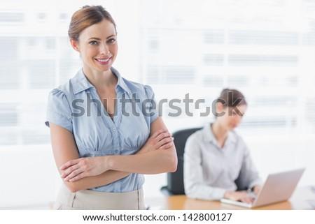 Smiling businesswoman with arms crossed with co worker working behind - stock photo