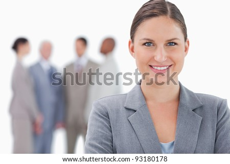 Smiling businesswoman with colleagues behind her against a white background - stock photo