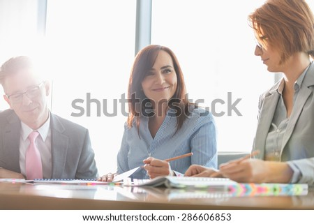Smiling businesswoman with colleagues in meeting room - stock photo