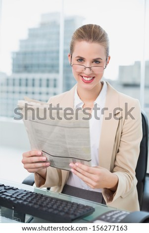 Smiling businesswoman with glasses reading newspaper in bright office - stock photo