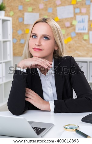 Smiling businesswoman with head on hand in front of computer. Office at background. Concept of work. - stock photo