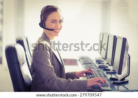 Smiling businesswoman with headset using computers in office - stock photo