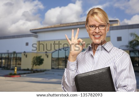 Smiling Businesswoman with Okay Sign In Front of Vacant Office Building. - stock photo