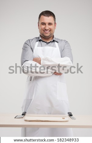 smiling butcher standing behind table. professional butcher and two knives on table - stock photo
