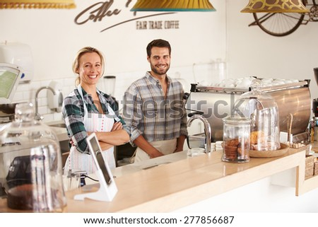 Smiling cafe workers in a coffee shop - stock photo