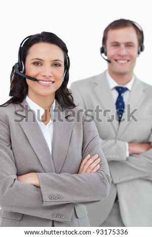 Smiling call center agents with headsets and arms folded against a white background - stock photo