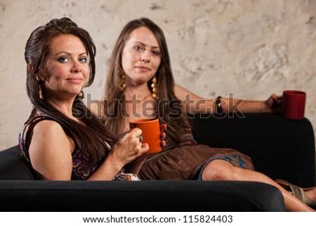 Smiling calm pair of women sitting on sofa holding coffee mugs - stock photo