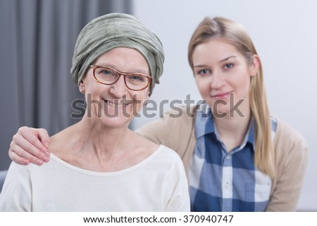 Smiling cancer woman with headscarf with young daughter - stock photo