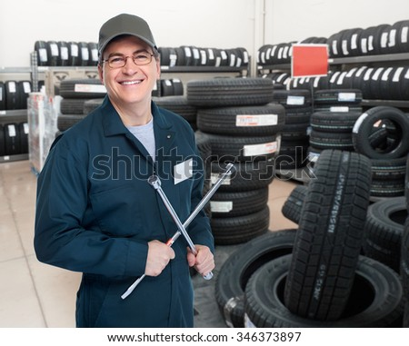 Smiling car mechanic with lug wrench over garage background. - stock photo