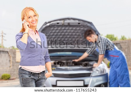 Smiling careless female talking on a mobile phone while in the background mechanic is checking her car - stock photo