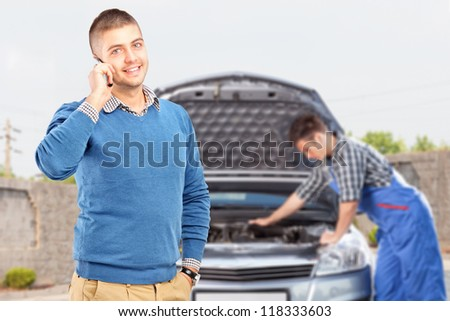 Smiling careless guy talking on a cell phone while in the background mechanic is checking his car - stock photo