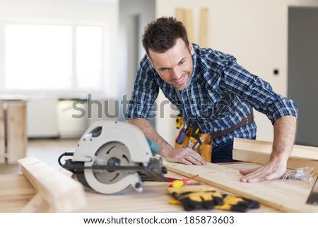 Smiling carpenter checking result of his work  - stock photo