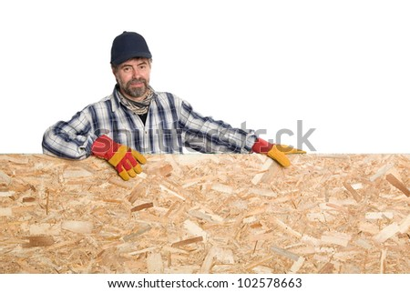 Smiling carpenter with a sheet of plywood. - stock photo