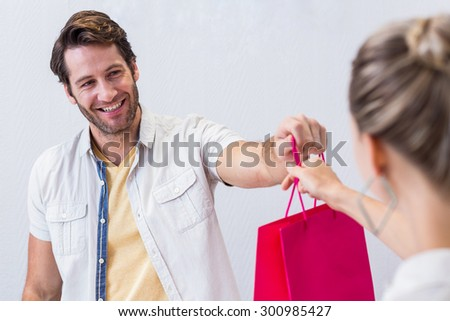 Smiling cashier giving shopping bag to woman in clothing store - stock photo