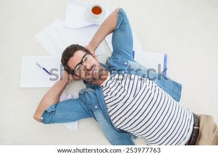 Smiling casual businessman lying on files in the office - stock photo