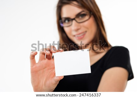 Smiling casual female in black t-shirt showing a business card - copy space. - stock photo